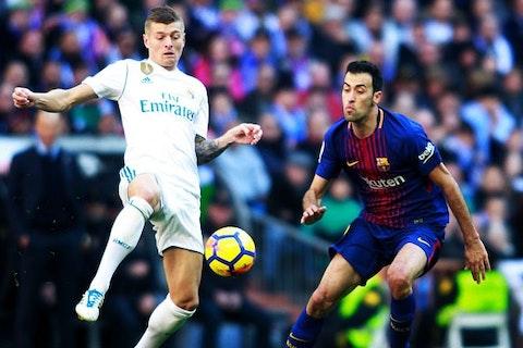 Immagine dell'articolo: https://image-service.onefootball.com/crop/face?h=810&image=https%3A%2F%2Fwww.calcionews24.com%2Fwp-content%2Fuploads%2F2018%2F10%2FKroos-Busquets-real-madrid-barcellona-liga.jpg&q=25&w=1080